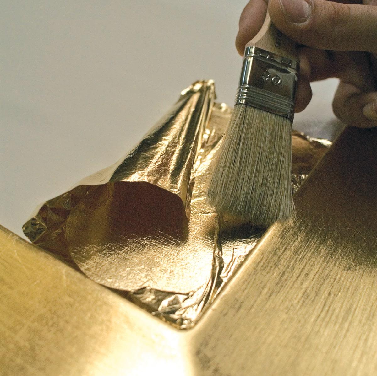 Finitura con foglia in oro su anta in legno